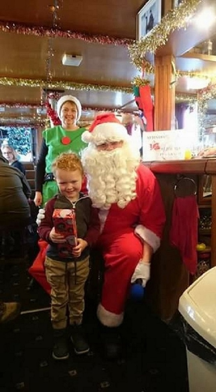 child with present standing next to santa with elf in background on board festive cruise boat