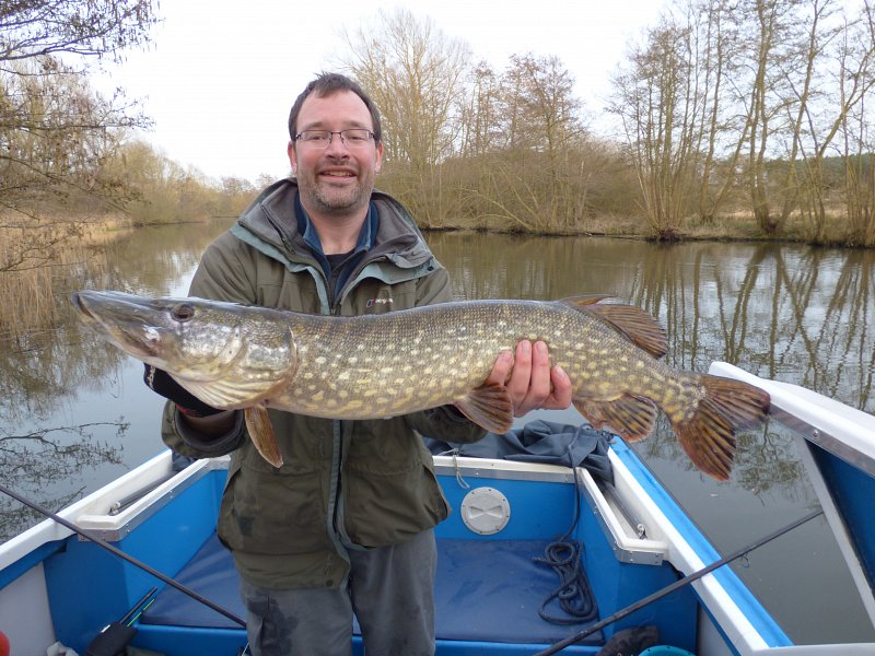 man holding large pike in day boat