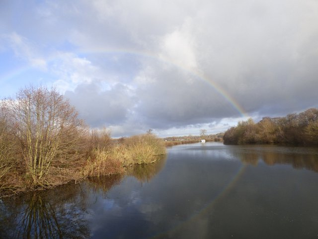 image of river with rainbow going from one bank to the other