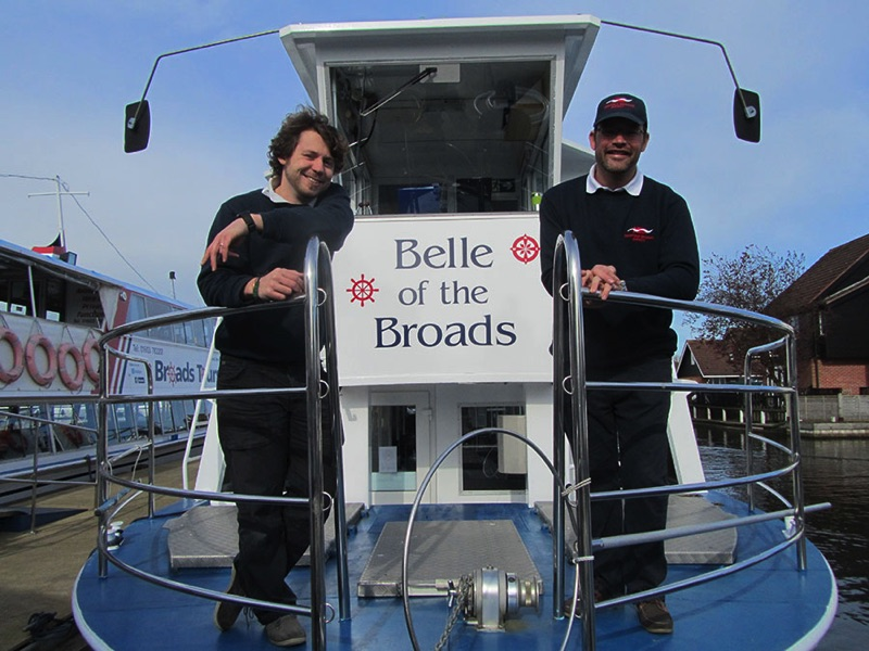 two men standing at the front of belle of the broads passenger trip boat