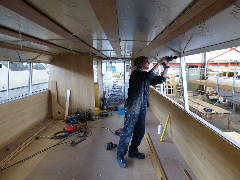 internal shot of man working on window frames of queen of the broads