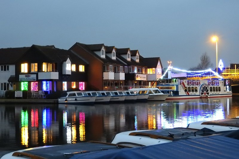 view of broads tours offices from across the water showing day boats lined up and vintage broadsman with festive lighting